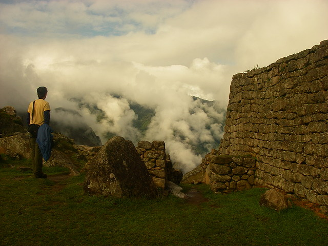 Turista gazing out into the valley from the top of Machu Picchu